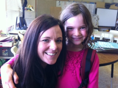 Avery hugs her teacher in the classroom the day before the class dissects owl pellets.