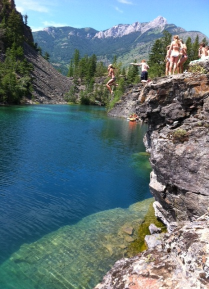 A teen jumps fearlessly off the highest cliff, plungng some tk feet intot he clear water below. Pristine Canadiana.