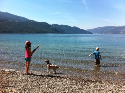 Kids and pup enjoy the clear blue water of Kalamalka Lake.