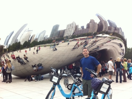 Blake pauses in front of Cloud Gate in Millennium Park, alongside his Divvy Bike.