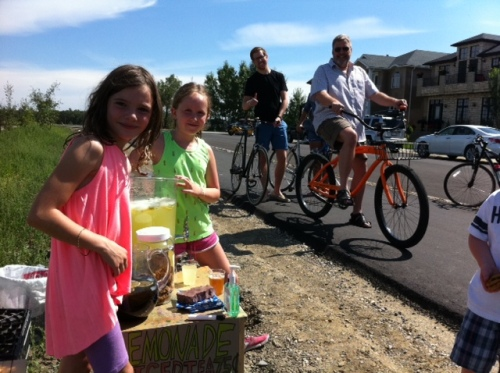 Cyclists line up for a cup of lemonade along the Bow River pathway in Inglewood on the weekend.
