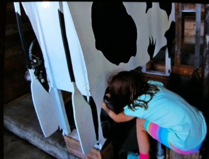 Avery milks a pretend cow at Sunnybrook Farm in Red Deer.