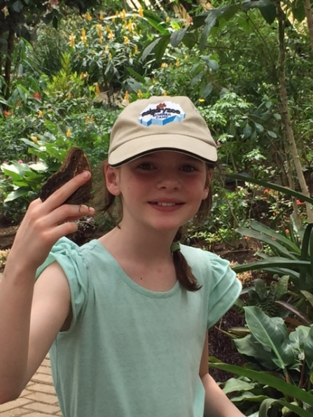 Avery holds a blue morpho butterfly inside the butterfly garden.