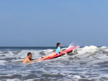 Rob pushes Avery out into the surf.