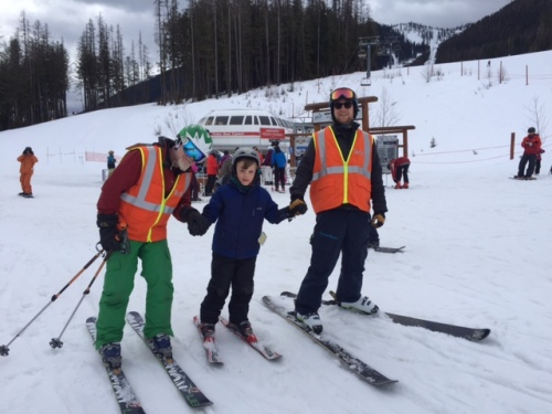 Volunteer instructors help Bennett ski to the chairlift.