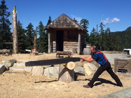A lumberjack competitor saws a log with his long saw at Grouse Mountain.